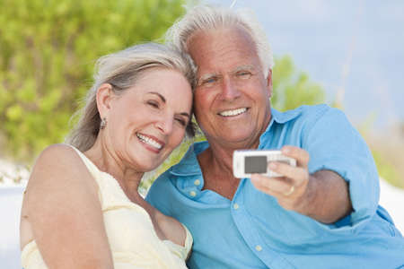 Happy senior man and woman couple laughing and taking photographs with a cell phone on a tropical beach