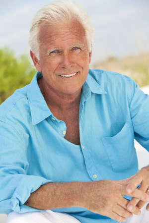 Portrait of a happy attractive handsome senior man sitting down outside and smiling Standard-Bild
