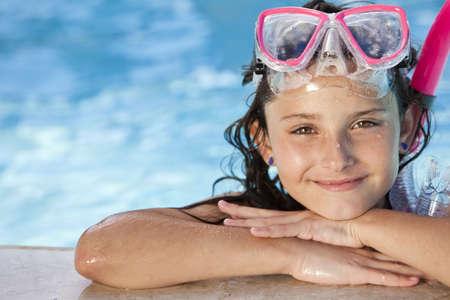 Un ni�o lindo ni�a feliz relajante al lado de una piscina que llevaba gafas de rosas y snorkel Foto de archivo