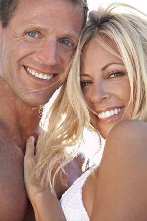 A sexy and attractive man and woman couple smiling and happy in the sunshine at the beach Stock Photo - 7127246