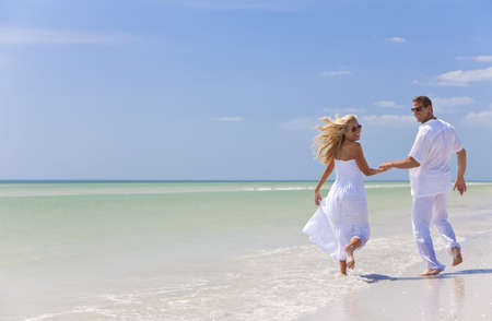 Happy young man and woman couple running, laughing and holding hands on a deserted tropical beach with bright clear blue sky Standard-Bild