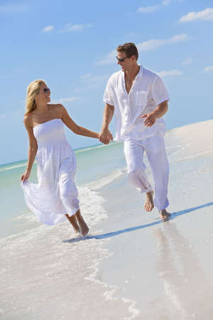 Happy young man and woman couple running, laughing and holding hands on a deserted tropical beach with bright clear blue sky Stock Photo
