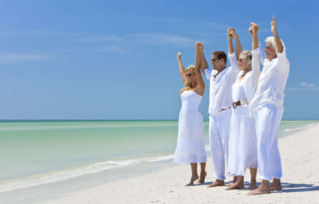 Two couples, generations of a family together holding hands and racing their arms in celebration on a deserted tropical beach Standard-Bild