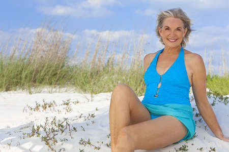 An attractive elegant senior woman in a blue swimming costume sitting on a white sand beach with grass and a blue sky behind her. photo