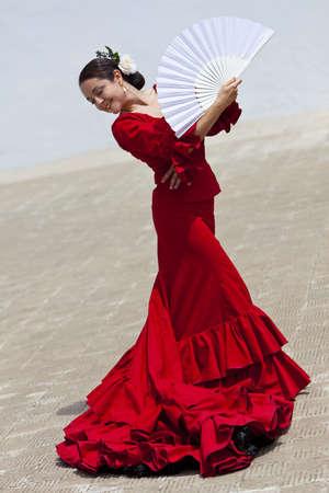 flamenco dancer: Bailar�n de flamenco espa�ol tradicional mujer bailando en un vestido rojo con un ventilador blanco Foto de archivo