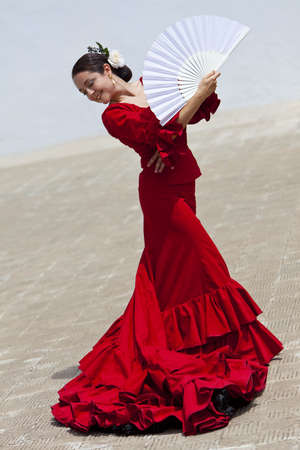 Woman traditional Spanish Flamenco dancer dancing in a red dress with a white fan