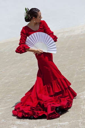 dancing pose: Woman traditional Spanish Flamenco dancer dancing in a red dress with a white fan