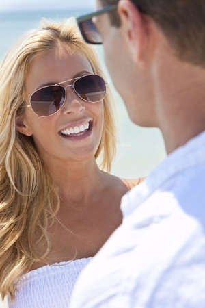 A sexy and attractive man and woman couple wearing sunglasses and having romantic fun laughing in the sunshine at the beach photo