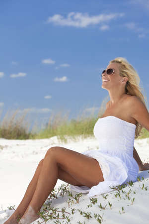 sundress: A beautiful young blond woman smiling in aviator sunglasses and a white sundress sitting on a deserted tropical beach Stock Photo