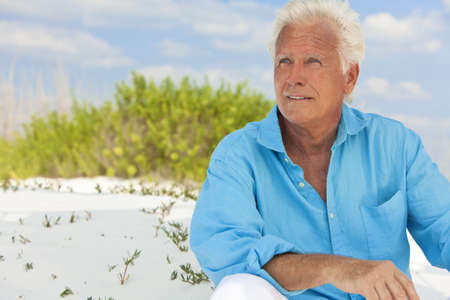 Portrait of a happy attractive handsome senior man sitting down outside on a white sand beach