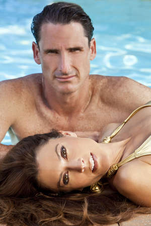 Portrait of a beautiful couple with a woman laying down at the side of a swimming pool with an attractive man behind her. The focus is on the woman in the foreground. photo