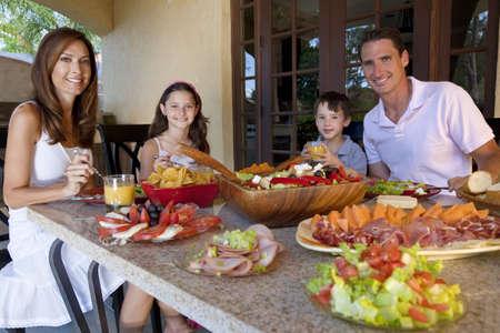 hombre comiendo: Una familia feliz y sonriente atractiva de madre, padre, hijo y su hija comer alimentos saludables con jam�n, queso y ensalada fresca en una mesa al aire libre en el hogar.
