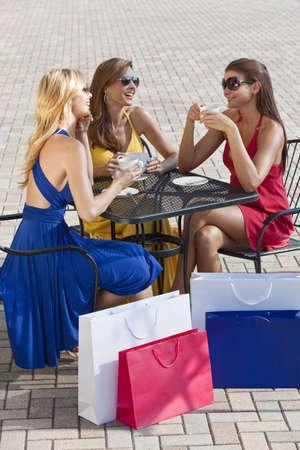 wealthy lifestyle: Tre giovani donne belle e sofisticati amici indossare occhiali da sole e avere caff� intorno a un caff� della citt� moderna tabella circondato da shopping bags