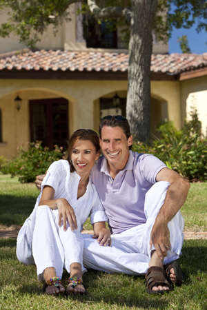 Portrait shot of an attractive, successful and happy middle aged man and woman couple in their thirties, sitting together outside under a tree and smiling.