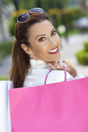 Beautiful, happy and fashionable woman with colorful pink and white shopping bags photo
