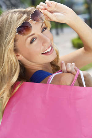 Beautiful, happy and fashionable young blond woman with heart shaped sunglasses and colorful shopping bags over her shoulder. photo