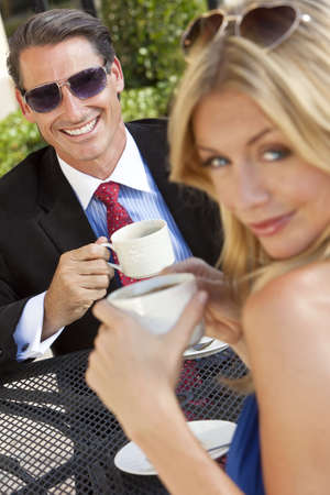 togther: An happy handsome businessman and attractive woman couple having coffee togther at an outdoor cafe or retsaurant table