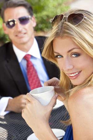 wealthy lifestyle: Una giovane donna bella e sofisticata avendo caff� a un tavolo di caffetteria moderna citt� con il suo amico un imprenditore vestito intelligente