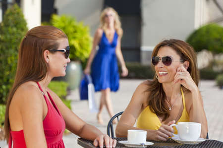 three friends: Two beautiful and sophisticated young women friends wearing sunglasses and having coffee around a modern city cafe table With their friend arriving with shopping bags in the background