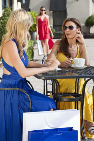 Two beautiful and sophisticated young women friends wearing sunglasses and having coffee around a modern city cafe table surrounded by shopping bags with their friend joining them in the background Standard-Bild