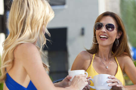 Two beautiful young woman outside at a city cafe laughing and drinking coffee Stock Photo - 7227813