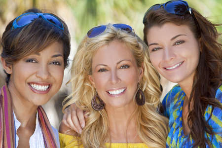 women laughing: Three beautiful young women in their twenties laughing and having fun on vacation, shot in golden sunshine in a tropical resort location. Stock Photo