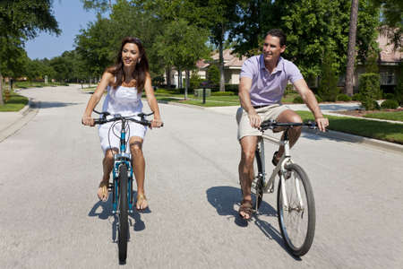 Two attractive adults, man and woman couple, cycling together, shot with a slow shutter speed and motion blur. Stock Photo - 7227821