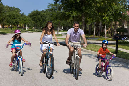 A modern family of two parents and two children, a boy and a girl, cycling together. photo