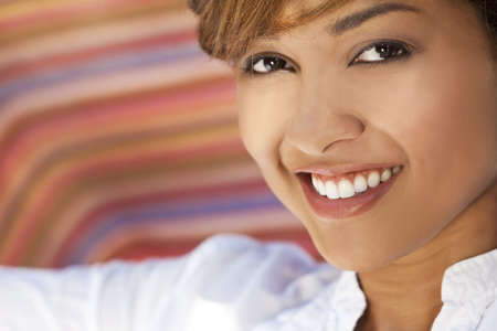 A beautiful mixed race young woman with perfect teeth and smile photo
