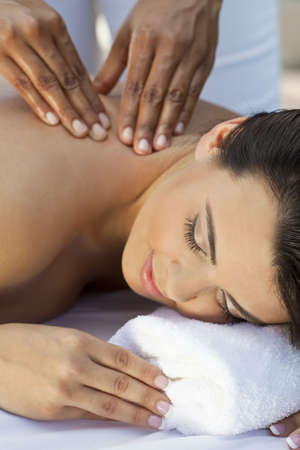 A young woman relaxing at a health spa while having a massage Stock Photo - 7256444