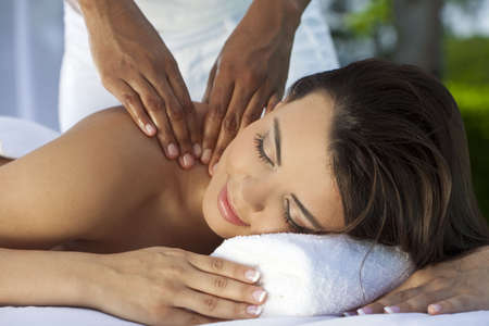 A young woman relaxing outside at a health spa while having a massage with a natural green background Stock Photo - 7256448