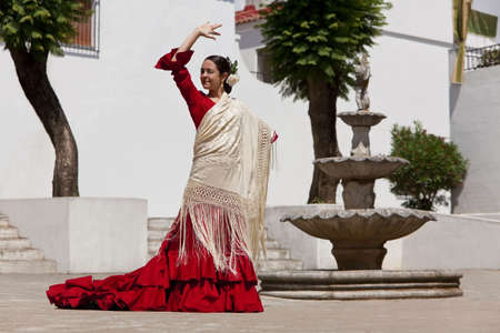 Woman traditional Spanish Flamenco dancer dancing in a red dress and cream shawl dancing in a town square with a stone fountain Standard-Bild