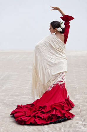 spanish girl: Woman traditional Spanish Flamenco dancer dancing outside in a red dress with a cream colored shawl Stock Photo