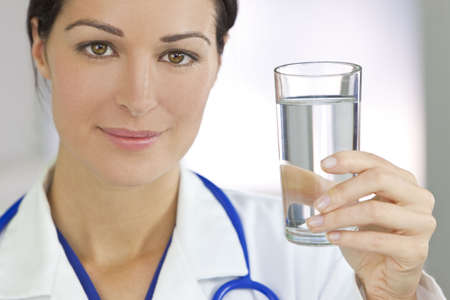 Healthy eating or lifestyle concept shot of a smiling female woman doctor holding and a glass of clear fresh water Standard-Bild