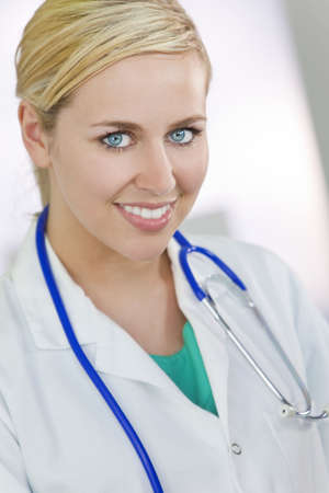 white coat: An attractive smiling female doctor wearing a white coat and stethoscope in a hospital.