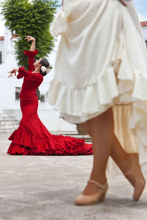 square dancing: Two women traditional Spanish Flamenco dancers dancing in a town square, the focus is on the dancer in the red dress
