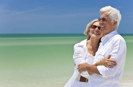 dating and romance: Happy senior man and woman couple together looking out to sea on a deserted tropical beach with bright clear blue sky Stock Photo