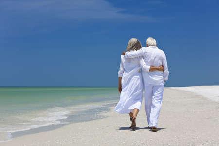 Achteraanzicht van een senior man en vrouw paar armen over elkaar op een verlaten tropisch strand met heldere blauwe lucht lopen