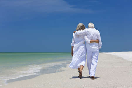 Rear view of a senior man and woman couple walking arms around each other on a deserted tropical beach with bright clear blue sky Standard-Bild