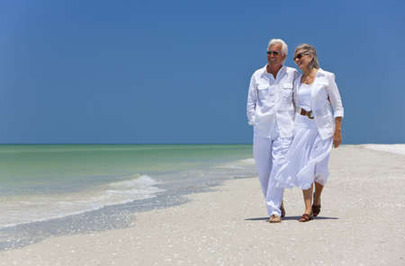 Romantic happy senior man and woman couple walking on a deserted tropical beach with bright clear blue sky