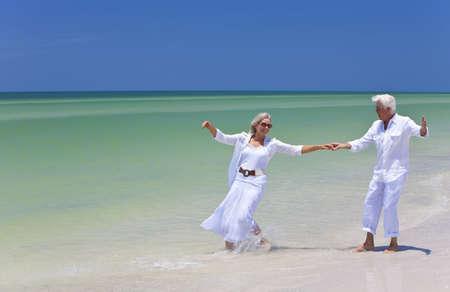 Feliz los pareja hombre y mujer senior bailar y celebrar las manos sobre una playa desierta tropical con brillante cielo azul claro
