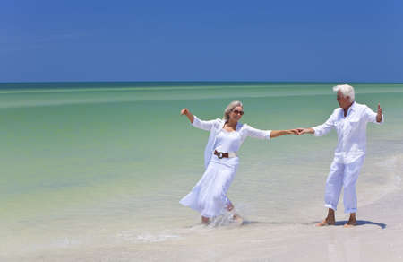 senior couples: Happy senior man and woman couple dancing and holding hands on a deserted tropical beach with bright clear blue sky