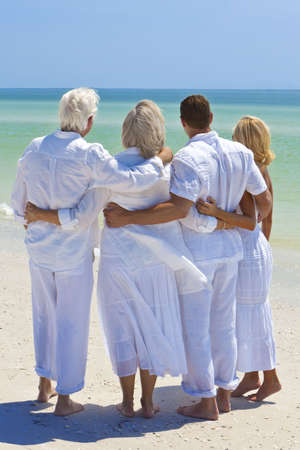 Two couples, generations of a family together embracing arms around each other in a hug on a tropical beach photo