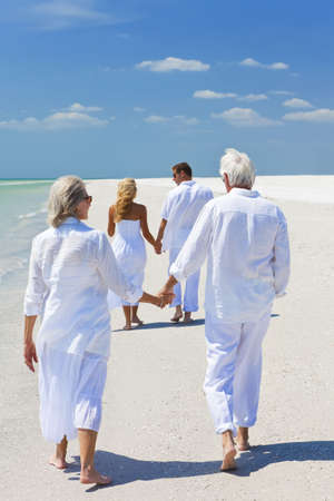 Two couples, generations of a family together holding hands and walking on a tropical beach Standard-Bild
