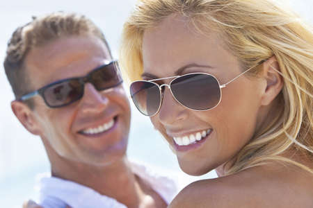 A happy and attractive man and woman couple wearing sunglasses and smiling in sunshine at the beach photo