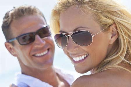 sunglasses: Un feliz y atractivo hombre y mujer par llevaba gafas de sol y sonriente en el sol en la playa  Foto de archivo