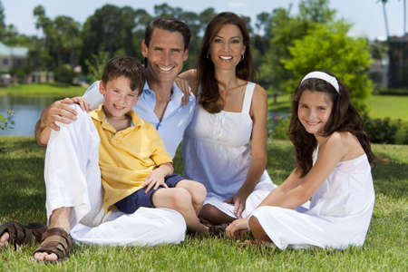 An attractive happy, smiling family of mother, father, son and daughter sitting on grass outside in warm summer sunshine Standard-Bild