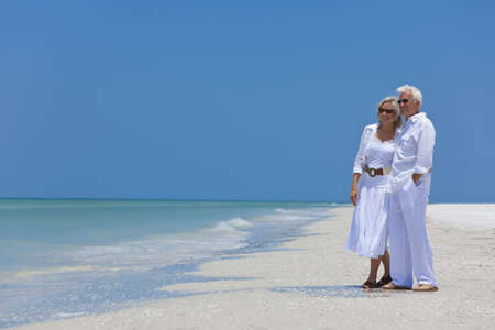 Happy senior man and woman couple together looking out to sea on a deserted tropical beach with bright clear blue sky Standard-Bild