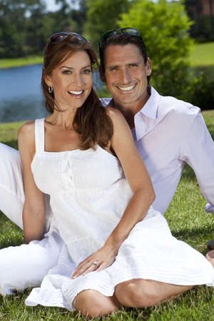 Portrait shot of an attractive, successful and happy middle aged man and woman couple in their thirties, sitting together outside by a lake and smiling. Standard-Bild