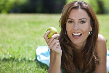 A beautiful woman in her thirties laying down outside on grass holding or eating an apple land smiling with perfect teeth